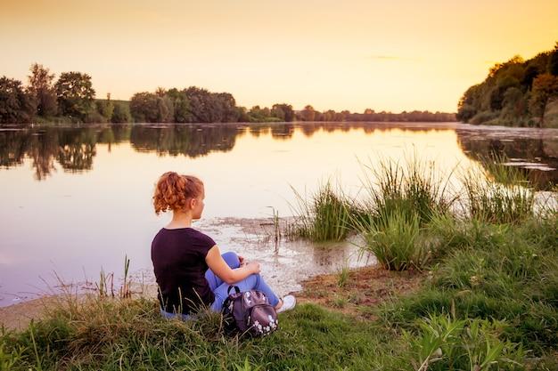 Giovane ragazza seduta sulla riva del fiume. la ragazza è nella natura. ammirando la bellezza della natura
