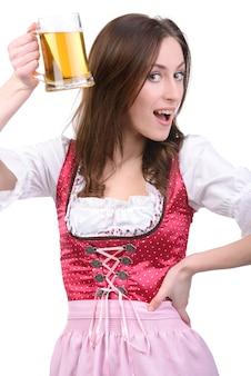Giovane ragazza sexy in abito nazionale con un bicchiere di birra.