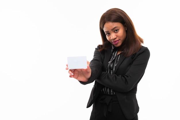 Giovane ragazza smilling dalla pelle scura che passa una carta isolata su bianco