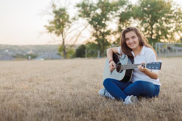 Giovane ragazza sorridente che canta alla chitarra