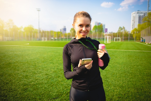 Giovane ragazza sorridente che fa forma fisica di sport e che corre nel parco facendo uso del suo telefono con le cuffie senza fili