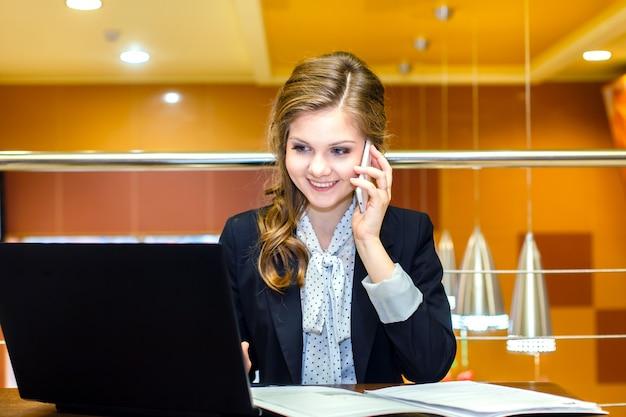 Giovane ragazza sorridente che si siede in un caffè con un computer portatile e che parla sul telefono cellulare