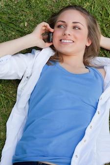 Giovane ragazza sorridente che si trova su lei indietro sull'erba mentre chiamando con il suo cellulare