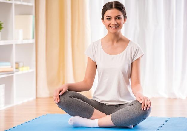 Giovane ragazza sorridente graziosa che fa yoga a casa.
