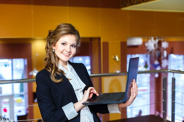 Giovane ragazza sorridente in piedi in un caffè e lavorando sul portatile