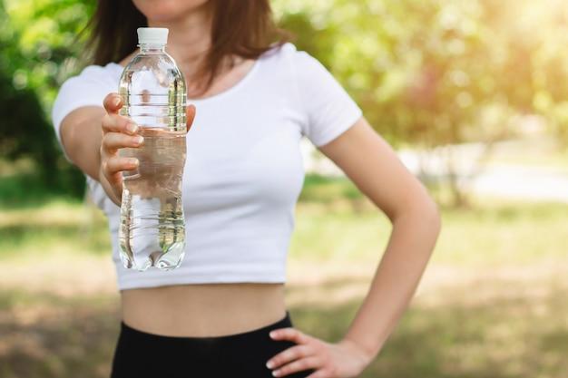 Giovane ragazza sottile in una maglietta bianca che tiene una bottiglia di acqua minerale.