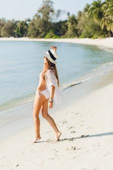 Giovane ragazza sottile sexy che balla su una spiaggia indossando costumi da bagno bikini bianco. indossa una camicia bianca, occhiali da sole scuri e un cappello di paglia. è abbronzata ed elegante.