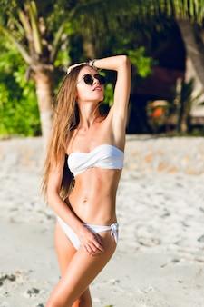 Giovane ragazza sottile sexy in piedi su una spiaggia indossando costumi da bagno bikini bianco. indossa occhiali da sole scuri e ha lunghi capelli scuri. è abbronzata ed elegante.