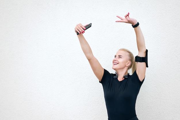 Giovane ragazza sportiva attraente che indossa abiti sportivi neri che ascolta la musica e che allunga sul fondo bianco della parete