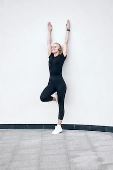 Giovane ragazza sportiva attraente che indossa abiti sportivi neri che ascolta la musica e che allunga sulla parete bianca. concetto di vita attiva e sana.