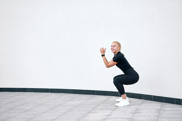 Giovane ragazza sportiva attraente che indossa addestramento nero degli abiti sportivi sulla parete bianca. concetto di vita attiva e sana.