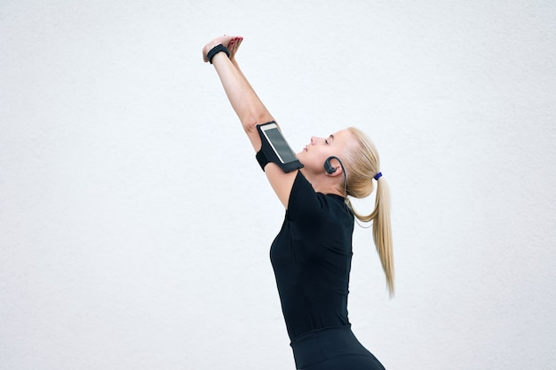 Giovane ragazza sportiva bionda che indossa abiti sportivi neri che ascolta la musica e che allunga sulla parete bianca. concetto di vita attiva e sana.