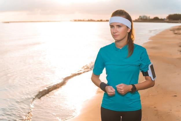 Giovane ragazza sportiva in esecuzione sulla spiaggia all'alba in mattinata