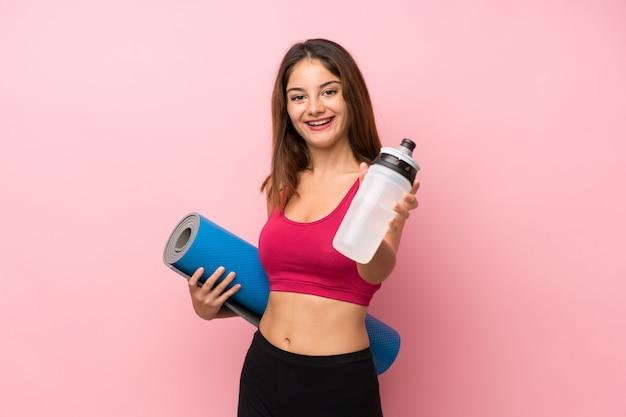 Giovane ragazza sportiva sopra rosa isolato con bottiglia d'acqua sport e con una stuoia
