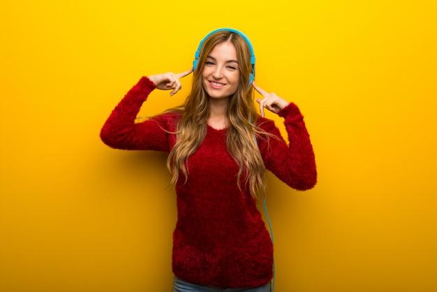 Giovane ragazza su giallo vibrante ascoltando musica con le cuffie
