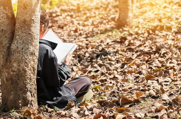 Giovane ragazza sveglia asiatica felice attraente che legge e che studia studiando sotto gli alberi
