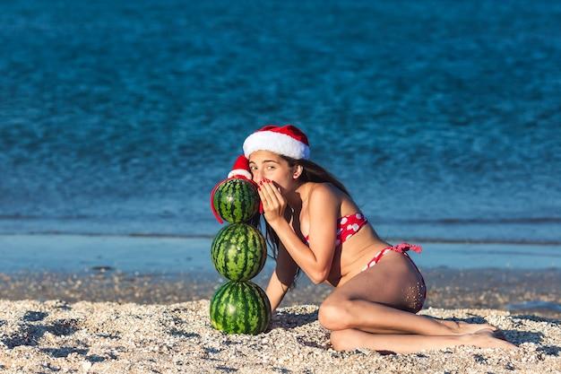 Giovane ragazza teenager che bisbiglia qualcosa al pupazzo di neve dalle angurie. natale estivo sulla spiaggia.