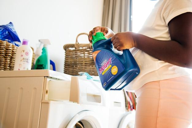 Giovane ragazza teenager che lava i vestiti facendo uso della lavatrice
