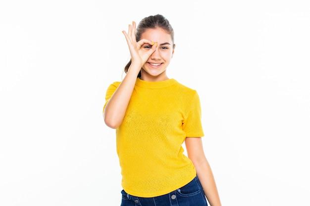 Giovane ragazza teenager con il gesto giusto di divertimento isolato sulla parete bianca