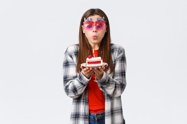 Giovane ragazza tenera b-day tenera sveglia in vetri, soffiando candela accesa sulla torta di compleanno, facendo desiderio e celebrando alla festa, fondo bianco