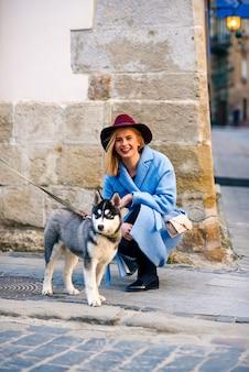 Giovane ragazza turistica felice con un sorriso felice in un cappotto blu e cappello bordeaux con husky di razza giovane cane in strada