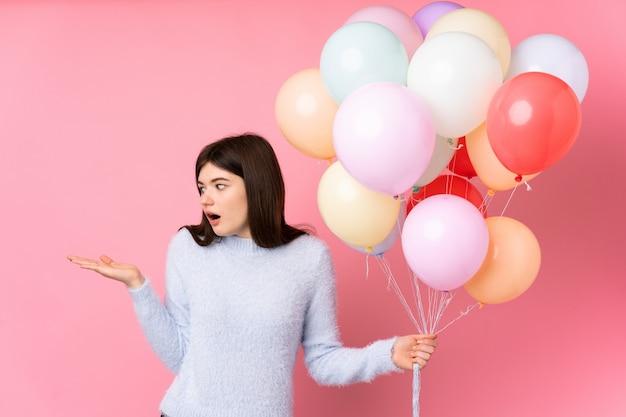 Giovane ragazza ucraina dell'adolescente che tiene i lotti dei palloni sopra il copyspace rosa della tenuta della parete immaginario sulla palma