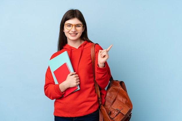Giovane ragazza ucraina dello studente dell'adolescente che tiene un'insalata sopra la parete blu isolata che indica dito il lato