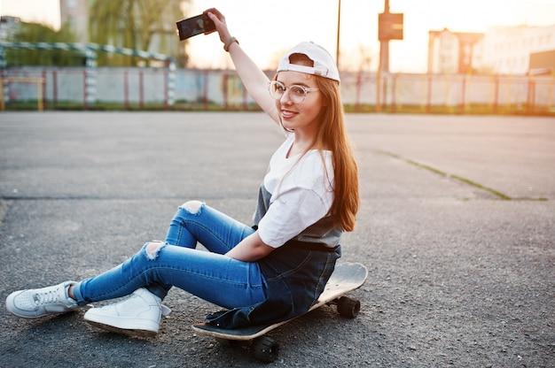 Giovane ragazza urbana adolescente con skateboard, indossare occhiali, berretto e jeans strappati al campo sportivo del cortile sul tramonto facendo selfie sul telefono.