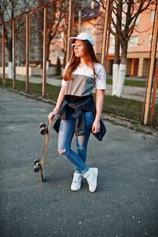 Giovane ragazza urbana adolescente con skateboard, indossare occhiali, berretto e jeans strappati al campo sportivo del cortile.