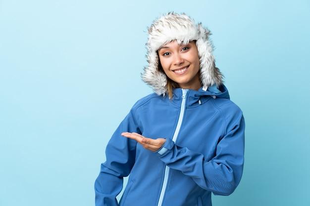 Giovane ragazza uruguaiana con cappello invernale isolato su blu allungando le mani a lato per invitare a venire