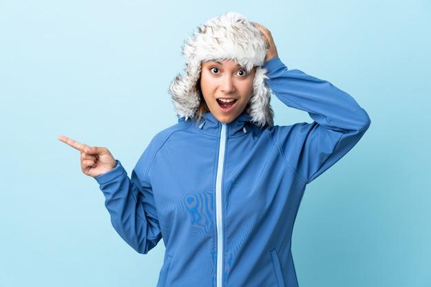 Giovane ragazza uruguaiana con cappello invernale isolato su blu sorpreso e puntando il dito verso il lato