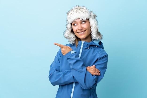 Giovane ragazza uruguaiana con cappello invernale sul dito blu wallpointing al lato