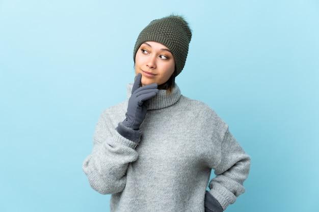 Giovane ragazza uruguaiana con il cappello di inverno isolato sul blu che pensa un'idea