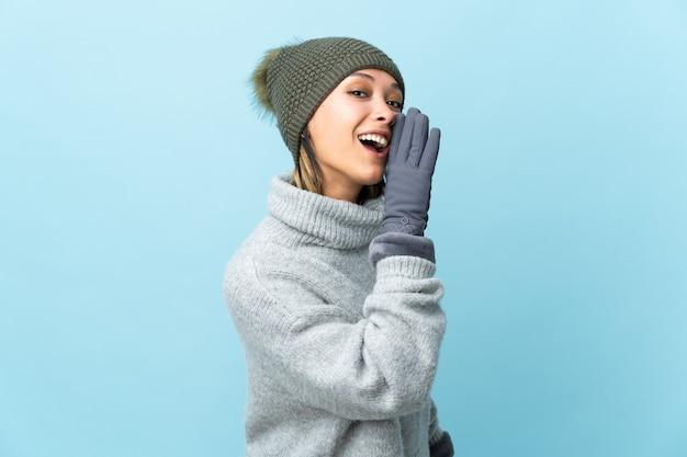 Giovane ragazza uruguaiana con il cappello di inverno isolato sulla parete blu che bisbiglia qualcosa