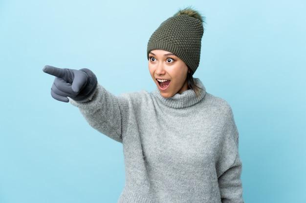 Giovane ragazza uruguaiana con il cappello di inverno sulla parete blu che indica via