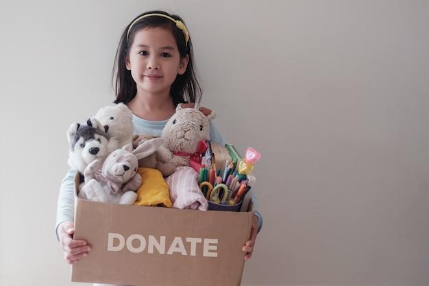 Giovane ragazza volontaria asiatica mista che tiene una scatola piena di giocattoli, panni, libri e articoli di cancelleria usati per donazione