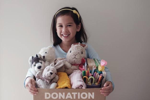 Giovane ragazza volontaria mista che giudica una scatola piena di giocattoli usati