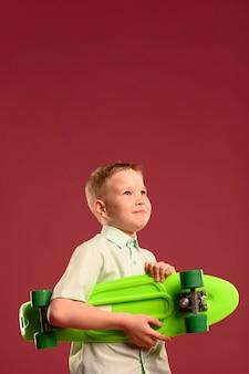 Giovane ragazzo adorabile con lo skateboard che osserva via