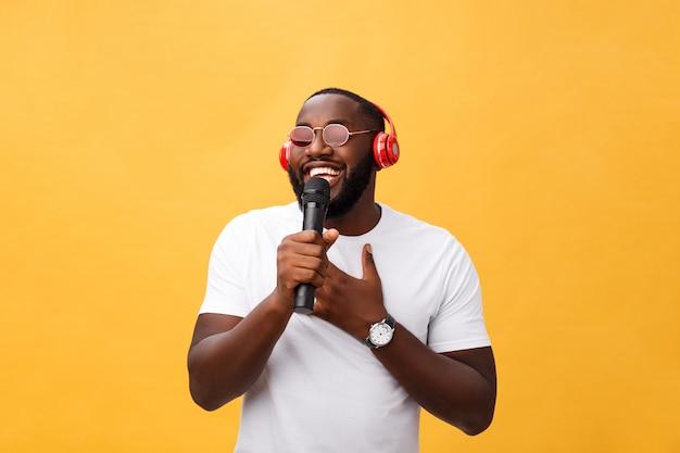 Giovane ragazzo afroamericano bello che canta emozionale con il micro