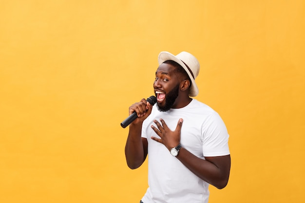 Giovane ragazzo afroamericano bello che canta emozionale con il microfono isolato su fondo giallo