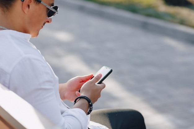 Giovane ragazzo alla moda in camicia con il telefono sul banco in giornata di sole all'aperto
