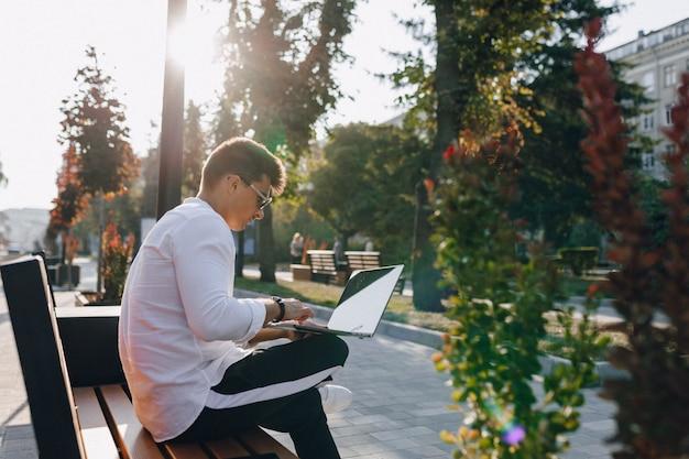 Giovane ragazzo alla moda in camicia con telefono e notebook sul banco in giornata di sole all'aperto