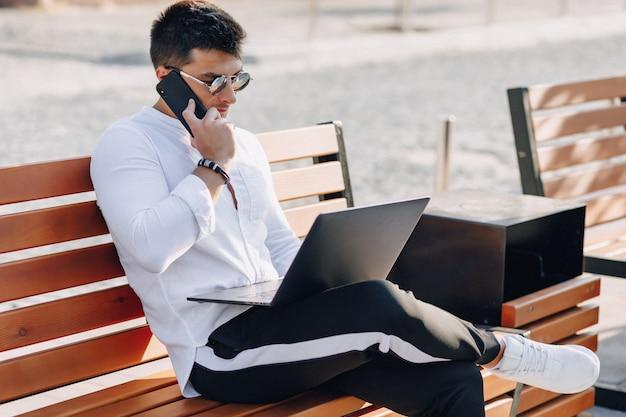 Giovane ragazzo alla moda in camicia con telefono e notebook sul banco in giornata di sole caldo all'aperto, libero professionista