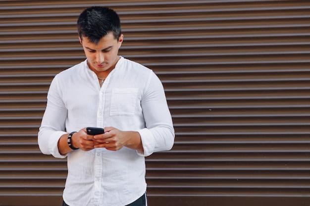 Giovane ragazzo alla moda in camicia digitando sul telefono su semplice
