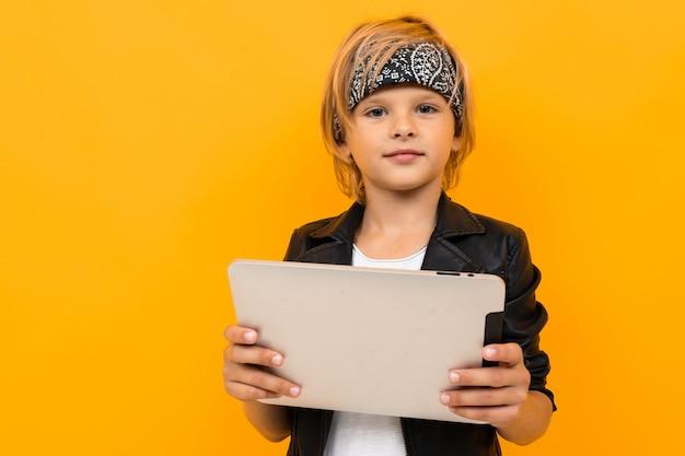 Giovane ragazzo alla moda in giacca nera e maglietta bianca che servisce internet con il suo tablet
