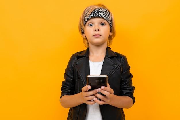 Giovane ragazzo alla moda in giacca nera e maglietta bianca che servisce internet con il suo telefono