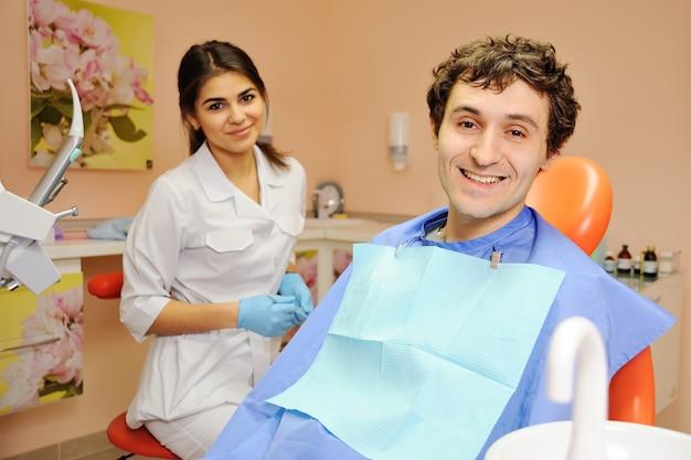 Giovane ragazzo alla reception presso la ragazza del dentista
