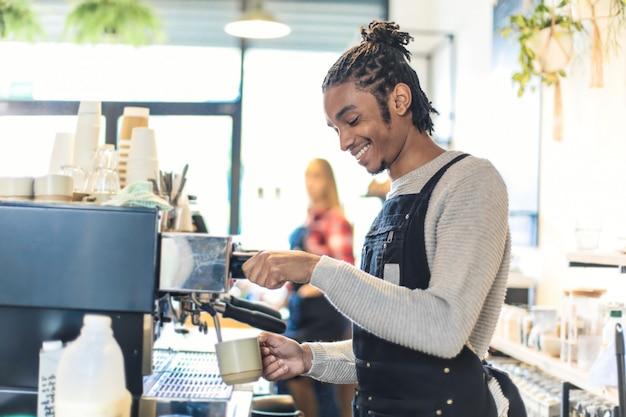 Giovane ragazzo allegro che prepara il caffè con la macchina del caffè