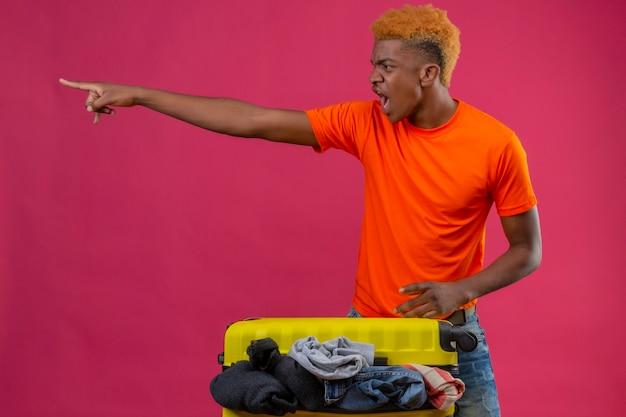 Giovane ragazzo arrabbiato che indossa la maglietta arancione in piedi con la valigia di viaggio piena di vestiti