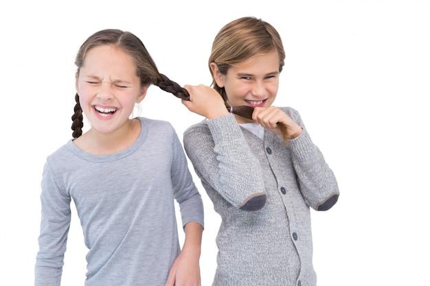 Giovane ragazzo arrabbiato che tira i capelli della sorella in una lotta